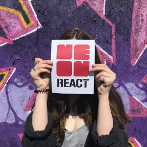 Photograph of a woman standing in front of a graffiti board holding the NEoN REACT logo infront of her face.