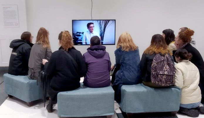 A group of students sit on grey cubes in a white room, watching a video artwork on a small screen. The video artwork is Utopia Generator by artist Julia Schicker, and the screen shows a white man in glasses in mid-sentence. The mood is one of concentration.
