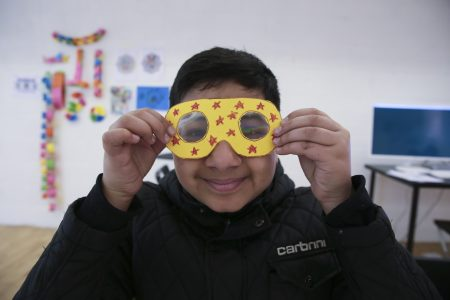 Young boy wearing a black jacket, holding up yellow fractal googles in front of his face and smiling. The googles are yellow and have been decorated with red stars