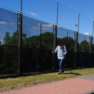 B.D. Owens walks alongside the fence at Faslane naval base, marking the #UndesiredLine with his modified shoes and hiking sticks